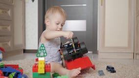 在家使用与在地板上的一个大汽车玩具的可爱宝宝男孩 哄骗使用与玩具汽车的男孩小孩户内 未来司机 股票录像