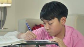 在家做与手提电脑的亚裔逗人喜爱的男孩家庭作业 股票视频