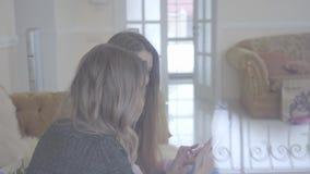 在家坐沙发和采取在他们的电话的两名俏丽的妇女selfie 女孩选择好照片 休闲现代 影视素材