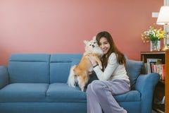 在家拿着她的在沙发的年轻亚裔妇女画象狗奇瓦瓦狗 免版税图库摄影