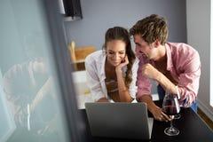 在家放松与膝上型计算机的年轻夫妇 爱、幸福、人们和乐趣概念 库存图片
