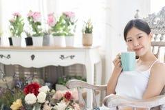 在家放松在木椅子的画象亚裔妇女用咖啡 免版税库存照片