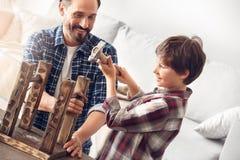 在家站立爸爸微笑的快乐的看的男孩的父亲和一点儿子锤击被集中的钉子 免版税图库摄影