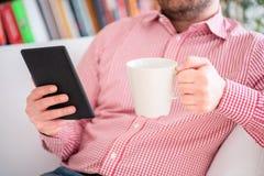 在家读一本新颖的畅销书在ebook读者 库存照片