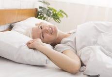 在家躺下在她的床上的成熟妇女 免版税图库摄影
