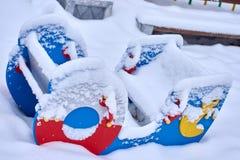 在寒冷冬天季节期间,关闭积雪的小船形状的跷跷板跷跷板动摇不定在儿童游戏公园 库存图片