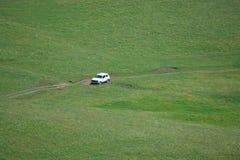 在小山的背景的白色汽车 库存图片