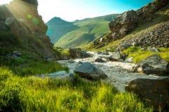 在山和在石头中的坚固性高地小河的脚的中午12点与天空蔚蓝的 库存照片