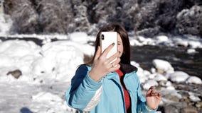 在山河附近的女孩在冬天森林里谈话在录影使用一个手机 影视素材