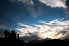 在山的美好的日落与人概述  免版税库存照片