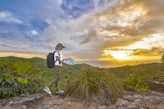 在山顶部的妇女游人在户外日落在一次远足期间在夏天 有背包的女孩旅客敬佩平静 库存图片