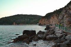 在岩石峭壁和锋利的石头附近的美好的海景在布德瓦黑山 游人的特别道路 令人惊讶的日落风景  图库摄影