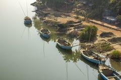 在岸的大蓝色渔船在反对绿色密林和小屋的光滑的水 免版税库存照片