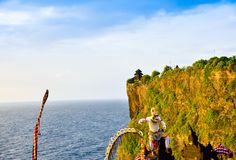 在峭壁的Goregeous浪漫日落在与神圣的寺庙的山顶部在顶面和白色猴子神字符 免版税库存图片