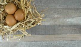 在巢的3个鸡鸡蛋有木背景 免版税库存照片