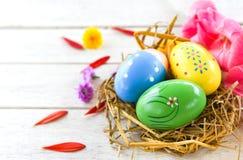 在巢装饰的复活节彩蛋与在白色的五颜六色的剑兰花瓣 免版税库存照片
