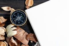 在干叶子和空白的笔记本上把放的金黄指南针在木减速火箭的黑桌上 复制文本和内容的空间 免版税图库摄影