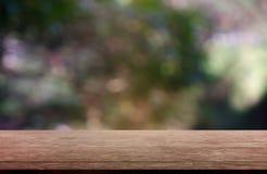 在庭院和自然光背景前面抽象被弄脏的绿色的空的木桌  对蒙太奇产品显示或设计 图库摄影