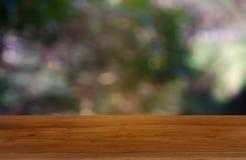 在庭院和自然光背景前面抽象被弄脏的绿色的空的木桌  对蒙太奇产品显示或设计 库存照片