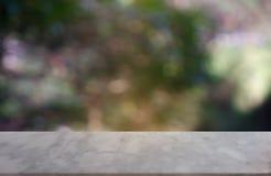 在庭院和自然光背景前面抽象被弄脏的绿色的空的marblestone桌  对蒙太奇产品显示或 免版税图库摄影