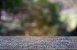 在庭院和自然光背景前面抽象被弄脏的绿色的空的marblestone桌  对蒙太奇产品显示或 库存照片