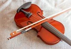 在床上的小提琴有织品背景 免版税图库摄影