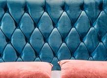 在床头板的长沙发型的丝绒冗长的句子拉紧与按钮 蓝色切斯特菲尔德样式缝制的室内装饰品背景关闭 免版税库存图片