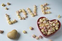 在心形碗的白色桃红色玉米花和书面'爱'用玉米花 免版税库存图片