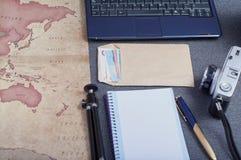 在地图、三脚架和金钱旁边信封的葡萄酒照相机在准备旅行的欧元 免版税库存图片