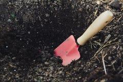 在土壤的手修平刀 库存照片