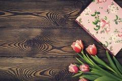 在土气桌上的礼物盒和郁金香花为3月8日,国际妇女天,生日或母亲节,美丽的春天卡片 库存照片