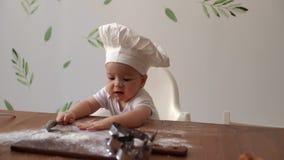 在厨师的盖帽的年轻逗人喜爱的孩子坐在木桌和口味面粉上 影视素材