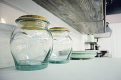 在厨房架子的空的玻璃容器 免版税图库摄影