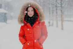 在冷淡期间,可爱的微笑的妇女射击的腰部有健康皮肤的,黑发,在口袋穿红色夹克,保留手 免版税库存照片