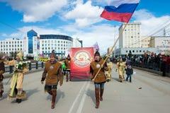 在全国服装的雅库特地区青年时期有俄国旗子的 免版税库存图片