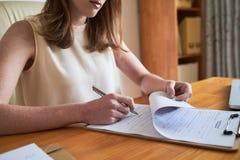 在剪贴板的妇女签署的纸 免版税库存图片