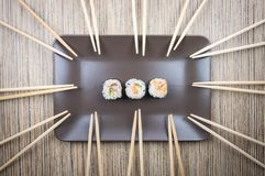 在板材的三寿司卷有许多的在木桌上的筷子 库存照片