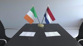 在桌上的爱尔兰和荷兰的旗子和纸 交涉和签署一项国际协定 皇族释放例证