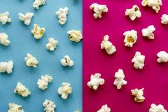 在桃红色和蓝色背景的玉米花 库存图片
