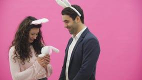 在桃红色背景的年轻性感的夫妇 使用在头的陈旧耳朵 在这个人期间给一个软的玩具用野兔 影视素材