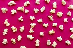 在桃红色背景的玉米花 库存照片
