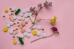 在桃红色背景的疏散多彩多姿的药片 医治草本 免版税库存照片