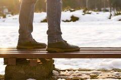 在棕色靴子和蓝色牛仔裤的男性腿在长木凳站立在被弄脏的背景的冬天好日子 做的概念 图库摄影