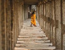 在橙色步行打扮的妇女在Virupaksha寺庙的寺庙柱子中间在hampi karnakata 库存图片