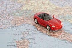 在欧洲地理地图的玩具红色汽车  旅行路线计划概念 库存照片