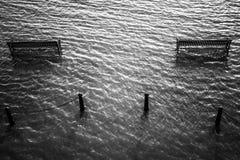 在水中围拢的长凳 免版税库存照片