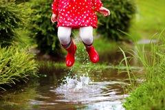 在水坑的孩子在秋天雨中 防水穿戴 免版税库存照片
