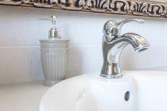 在水龙头水槽的肥皂和香波分配器与龙头在昂贵的顶楼卫生间里 图库摄影