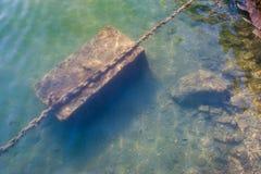 在水,船锚下的生锈的链子 停泊在岸 库存图片