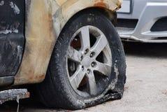 在汽车的被烧的泄了气的轮胎在灰色柏油路 库存照片